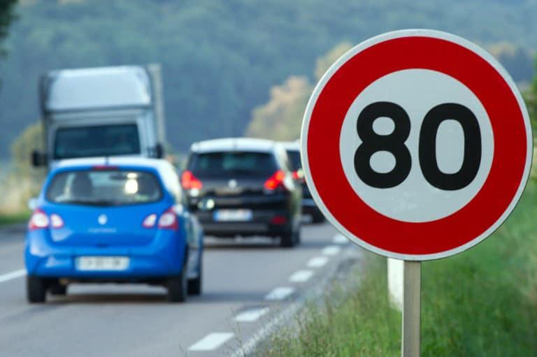 Photo d'un panneau de signalisation 80 km/h aux abords d'une route départementale